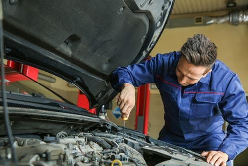 Automechaniker schraubt am Motor